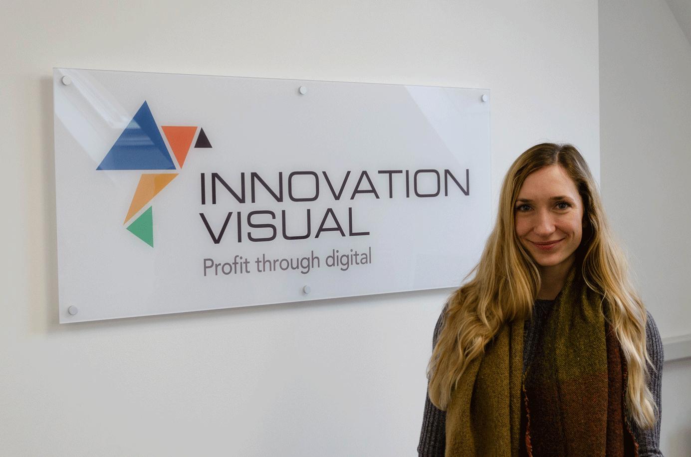 Miriam Gooch, Digital Marketing Executive for Innovation Visual in front of Innovation Visual Logo