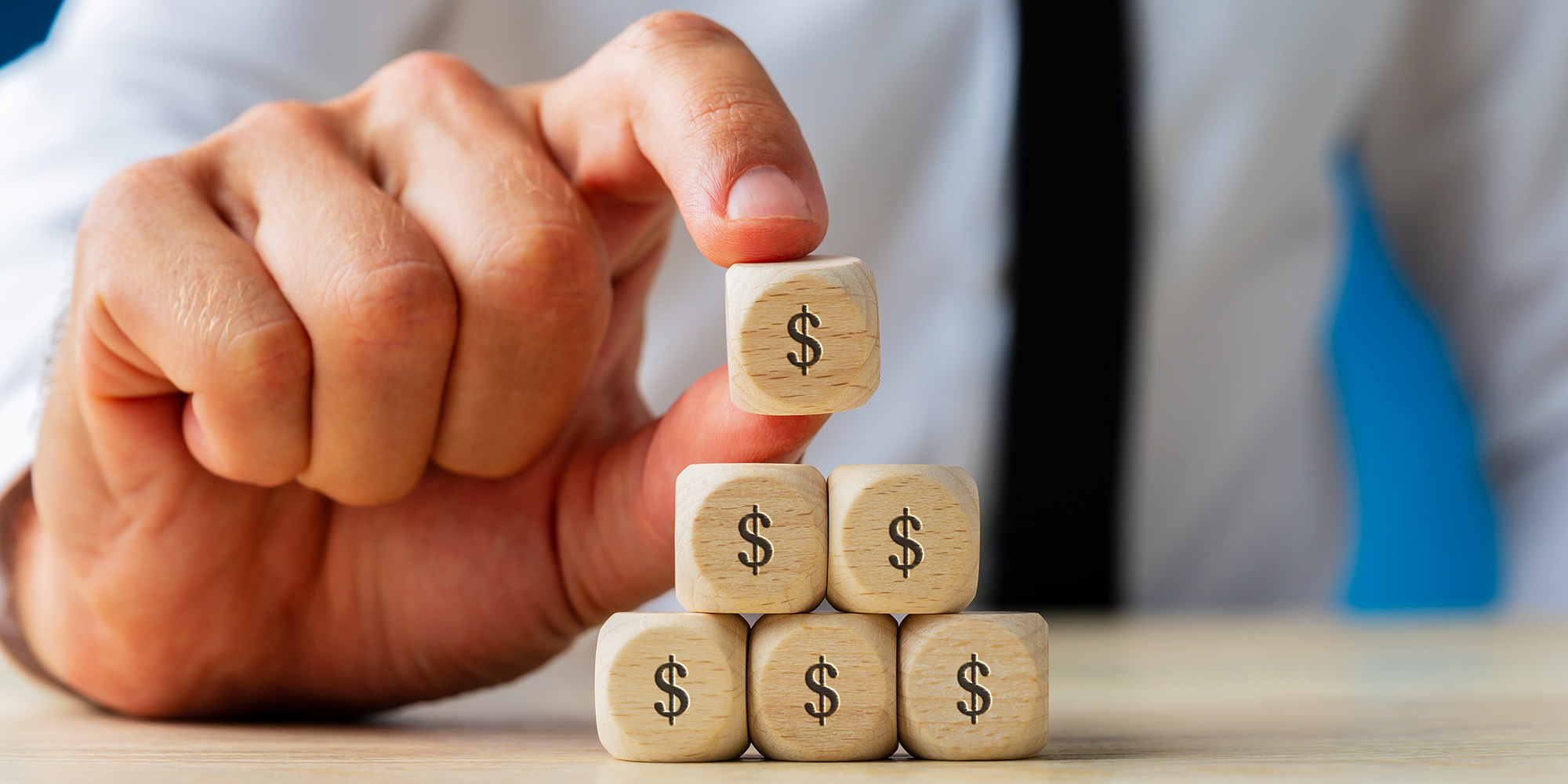 Business man stacks wooden dollar sign blocks conceptualising Conversion Rate Optimisation