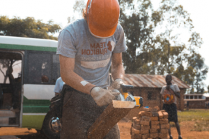 Construction worker cutting wood with a power tool