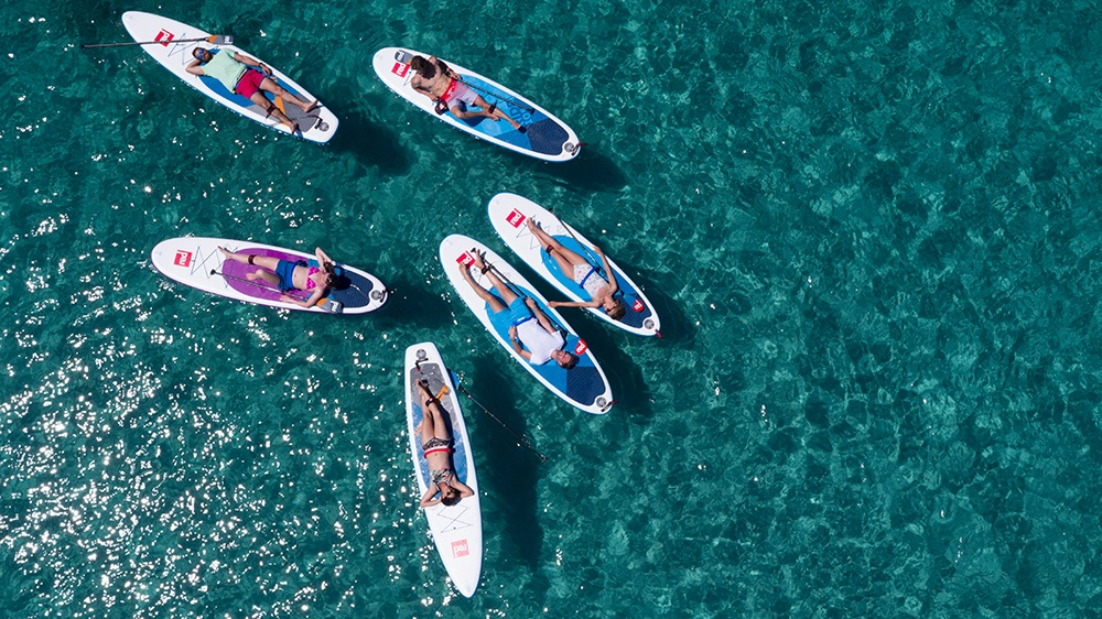 People laying on paddle boards in the water