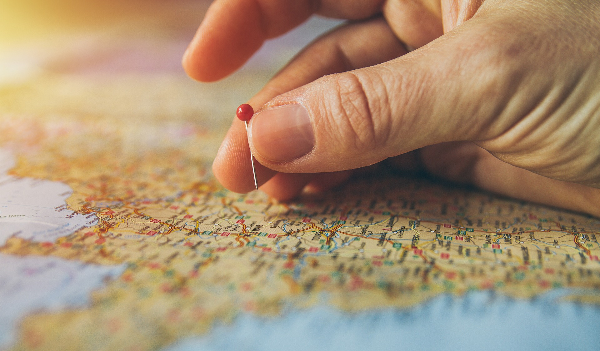 fingers holding a pin map of France