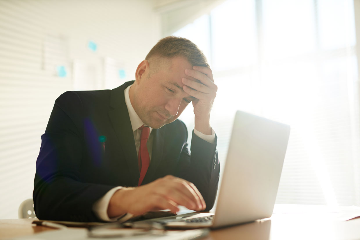Man with hands on head looks at low organic CTR data on laptop thinking of how to improve it